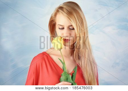 Beautiful young woman with tulip on color background