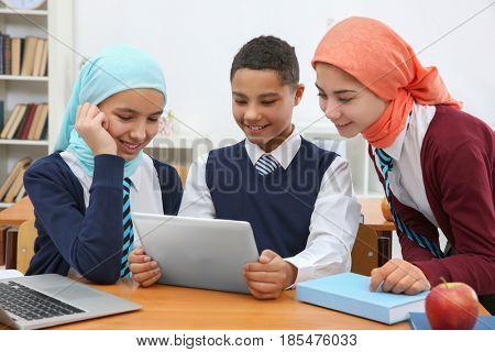 Schoolchildren using tablet at desk in classroom