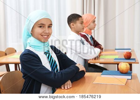 Cute girl sitting at desk in school class