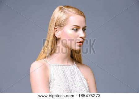 Beautiful young woman on grey background