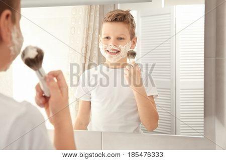 Cute boy with shaving foam on face near mirror in bathroom