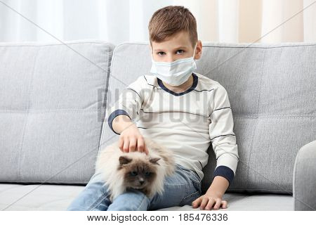 Animal allergy concept. Cute little boy with cat on sofa at home