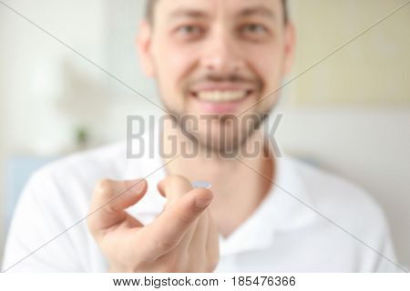 Hand of young man with contact lens, closeup