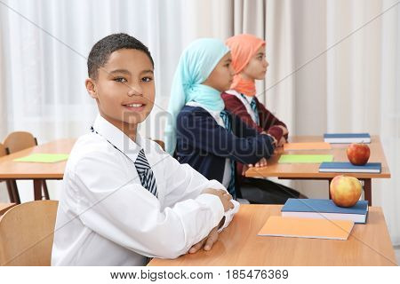 Cute boy sitting at desk in school class