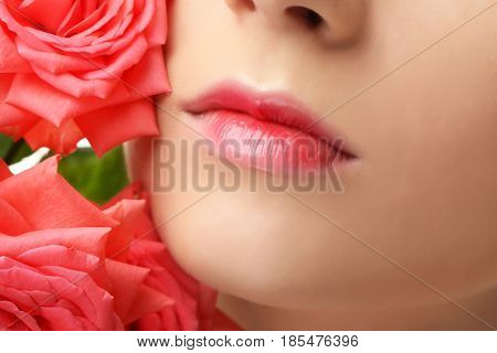 Face of beautiful young woman and roses, closeup
