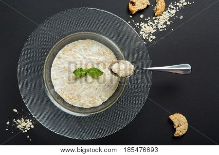 Healthy breakfast. Porridge or oatmeal with Leaf of mint isolated on black background. For a restaurant logo
