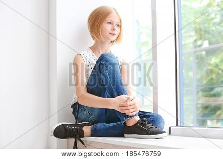 Cute teenager girl sitting near window