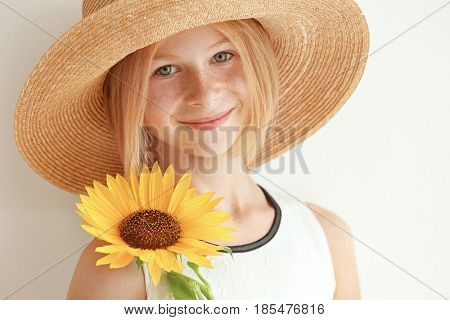 Portrait of attractive girl in straw hat with sunflower on white background