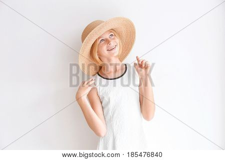 Cheerful teenager girl in straw hat on white background