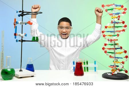 Happy school boy sitting at workplace in chemistry class