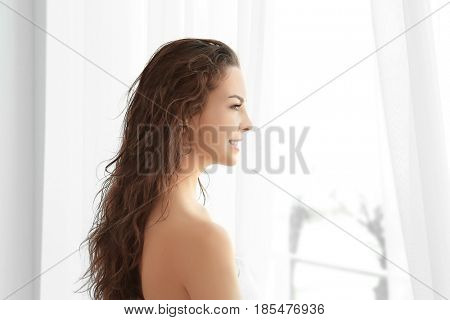 Beautiful young woman after shower standing near window at home
