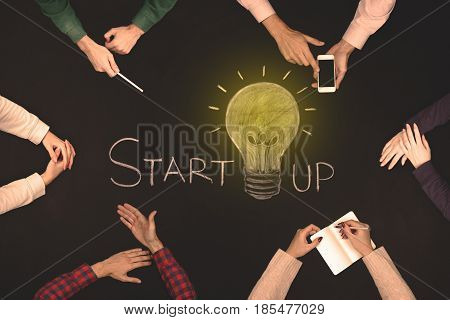 Teamwork startup concept - top view of six people. Blackboard table.