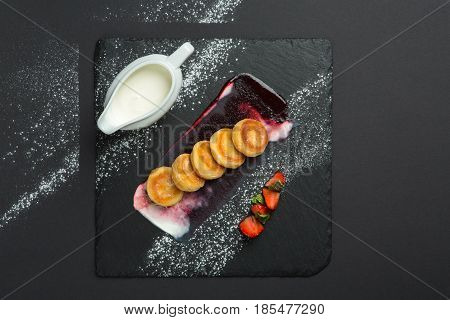 freshly baked cottage cheese pancakes with strawberries and sour cream on dark plate, top view