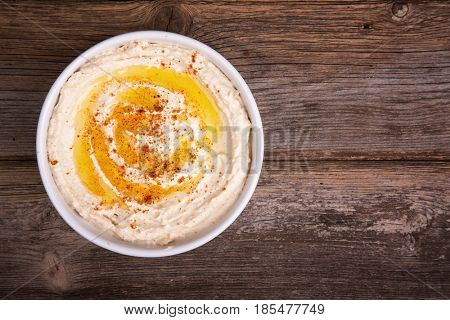 A bowl of fresh hummus, drizzled with olive oil and paprika, over old wood background.