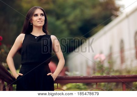 Elegant Woman Wearing Black Dress Standing in a Patio