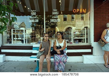 HARBOR SPRINGS, MICHIGAN / UNITED STATES - AUGUST 4, 2016: A woman and a girl sit on a bench in front of Howse's Fudge Shop on Main Street, in downtown Harbor Springs.