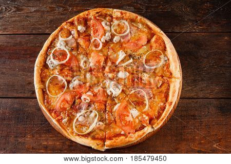 Junk food, unhealthy eating, bad habits, calories. Hot fresh baked pizza with ham, onion, tomato and cheese served on dark wooden table, flat lay.