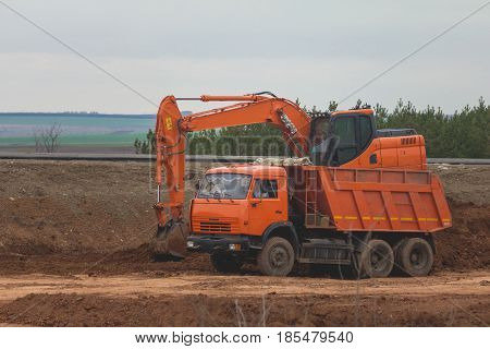 Heavy excavator loading dumper truck on road construction among fields, telephoto