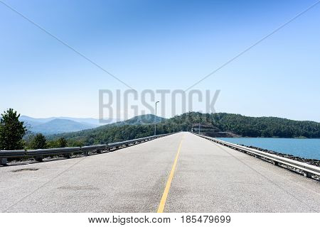 The crest road of Queen Sirikit Dam in Uttaradit Province Thailand in perspective view with blue sky