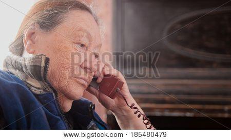 Portrait an old Woman pensioner speak landline phone, close up
