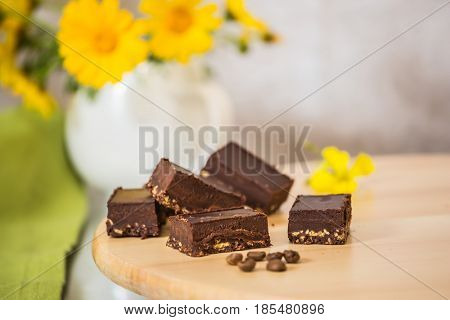 Gorgeous confectionery desserts. Portion small chocolate cakes with nuts filling. Background - a white vase with field chamomiles. Professional bakery