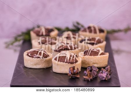 Magnificent portioned tartlet cakes with chocolate filling. Professional baking. Background black