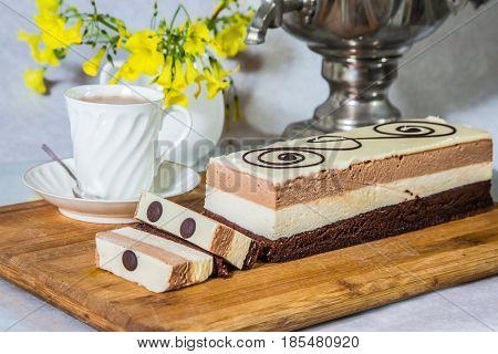 Three-layer chocolate cake, decorated with chocolate patterns. Cake Three-colate. Background - white vase with flowers and porcelain cup with hot tea. Professional bakery