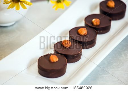 Portion small chocolate cakes are decorated with nuts. Background -  white vase with field chamomiles. Professional bakery