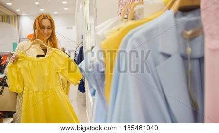 Adorable woman in a clothing store chooses a yellow dress - shopping concept, close up