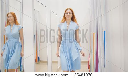 Young woman chooses blue dress near mirror in fitting room at store, middle shot