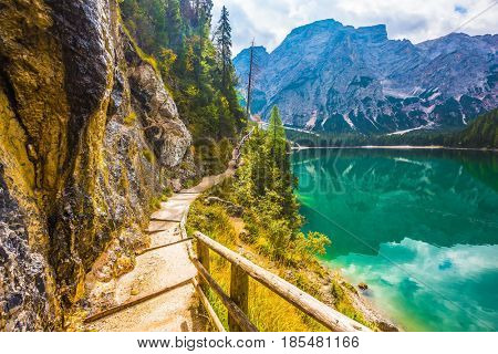 The concept of environmental and hiking. Walking trail around the lake is fenced with wooden railings. Magnificent Alpine lake Lago di Braies