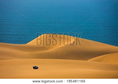 Dangerous and gorgeous jeep - safari through the huge sand dunes on the ocean shore. Atlantic coast of Namibia, south of Africa. The concept of exotic and extreme tours