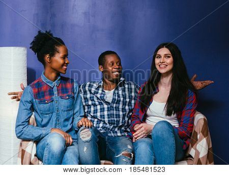 Happy company of three young friends together on pop blue background, international friendship. Smiling black man and two mixed races women sit at home on couch, fun pastime.