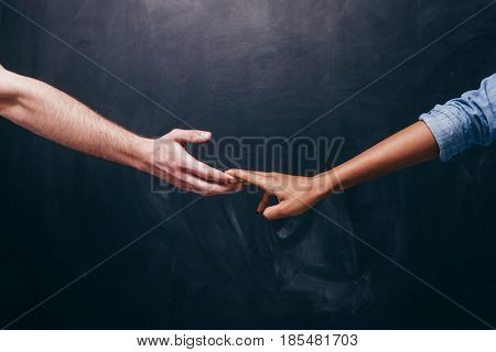 Reconnection of relationship or breakup.Two hands hold each other. Unrecognizable white guy and black woman on a dark background holding hands.