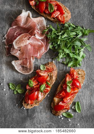 Delicious appetizers for wine or snack - cherry tomatoes bruschetta proscutto and arugula. Mediterranean style food. On wooden background top view