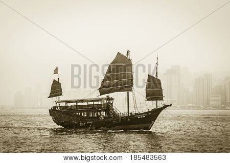 Hong Kong China - 27 January 2012: Traditional Chinese junk boat crossing Victoria Harbor