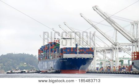 Oakland CA - May 05 2017: Large cargo ships are not able to maneuver sideways. Multiple tugboats push cargo ship CMA CGM A. LINCOLN sideways to the dock at the Port of Oakland.