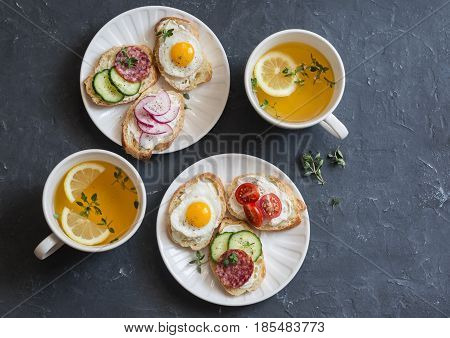 Mini sandwiches with cream cheese vegetables quail eggs salami and green tea with lemon and thyme. Sandwiches with cheese cucumber tomatoes radish thyme lemon zest fried quail eggs on a dark background top view. Delicious breakfast or snack