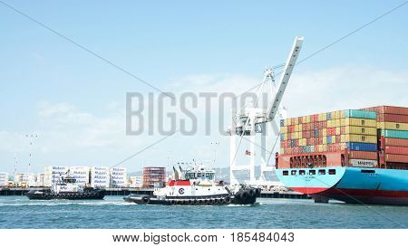 Oakland CA - May 06 2017: Tugboats VETERAN and REVOLUTION at the stern of cargo ship GUNDE MAERSK assisting the vessel to maneuver into the Port of Oakland.