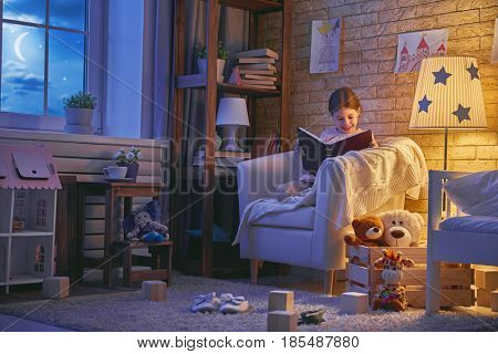 Cute little child girl reading a book under a lamp. Kid girl sitting in armchair near window in a dark moonlit night.