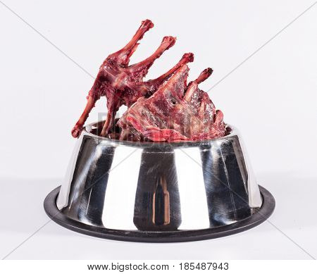 Dog´s metal bowl with raw beef ribbons isolated on white.