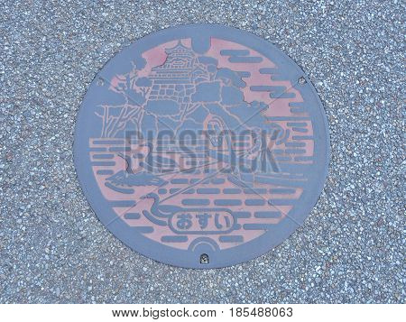 Aichi, Japan - February 18, 2017:A manhole cover of Inuyama, Aichi Prefecture, Japan. Ukai and Inuyama castle engraved on a manhole cover. Ukai is a traditional method of catching fish by cormorant.