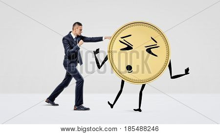 A businessman throwing punches at a big anthropomorphic coin with arms and legs. Hard-earned profit. Profitable investment. Experienced broker.