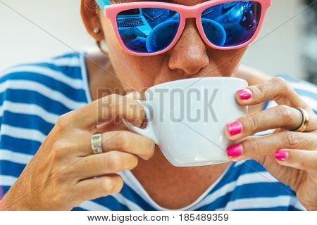 Adult woman wearing blue sunglasses having a cup of hot beverage.