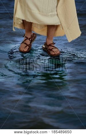 Feet of Jesus with sandals walking on the water