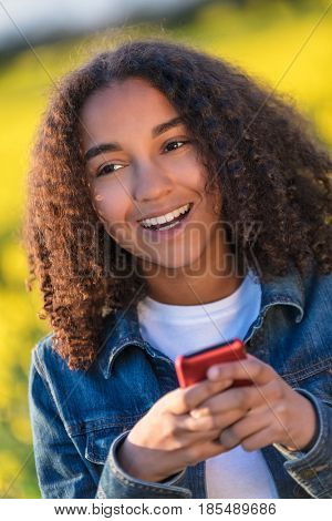 Outdoor portrait of beautiful happy mixed race African American girl teenager female young woman smiling with perfect teeth sending text on cell phone