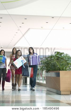 Hispanic friends carrying gifts in shopping mall