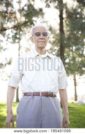 Senior Chinese man standing outdoors