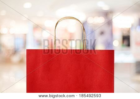 Red shopping bag over blurred store background business template retail sale