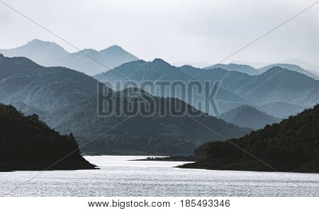 Dramatic scene of hazy mountains range with river inside tropical rainforest dam of Thailand.